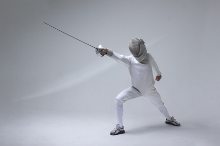 Professional fencer in fencing mask practising  with sword on grey background Zdjęcie Seryjne