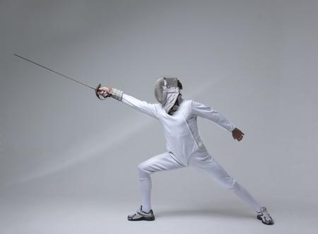 Professionele schermer in het schermen van masker oefenen met zwaard op grijze achtergrond