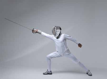 Professional fencer in fencing mask practising  with sword on grey background Archivio Fotografico
