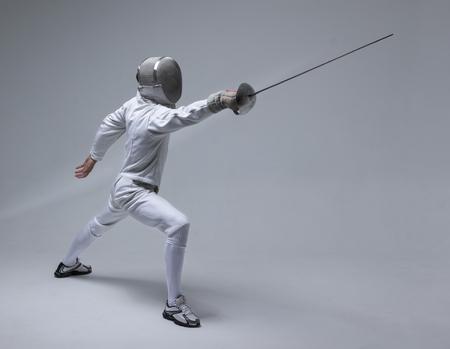 Esgrimista profesional en la máscara de esgrima practicando con espada sobre fondo gris Foto de archivo - 87669522