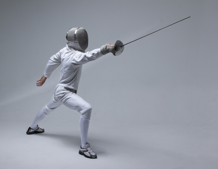 Professional fencer in fencing mask practising  with sword on grey background Stock Photo