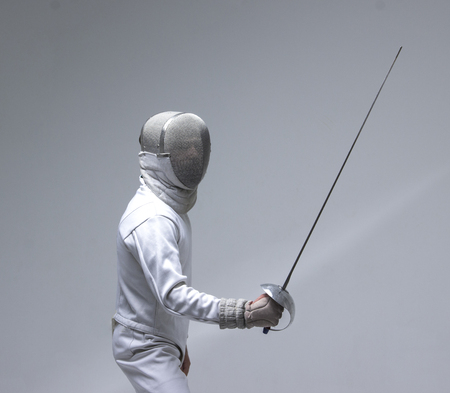 Man wearing fencing suit practicing with sword on grey background
