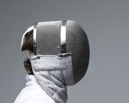 Profile of a fencer in fencing mask on grey background