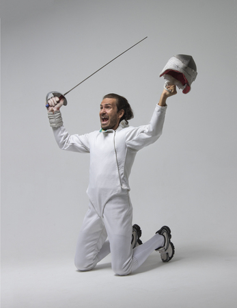 Portrait of a  fencer  with a sword holding his mask in all the glory.Celebrating the victory.Studio shot Stock Photo