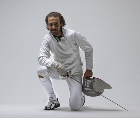Professional male cheerful fencer holding mask and sabre while staying on his knee. Studio shot Stock Photo