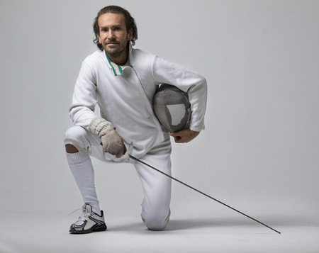 Professional male fencer holding mask and sabre while staying on his knee. Studio shot