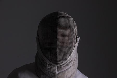 Portrait d'un escrimeur dans le masque d'escrime sur fond gris Banque d'images - 87669674