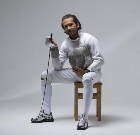 Escrimeur masculin professionnel tenant le masque et le sabre tout en étant assis sur une chaise. Studio tourné Banque d'images - 87669681