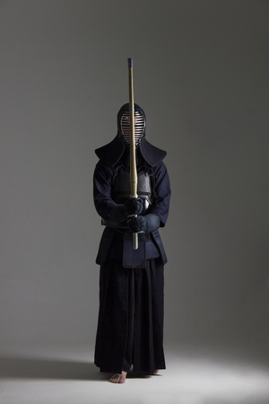 male in tradition kendo armor with shinai (bamboo sword). shot in studio on grey background