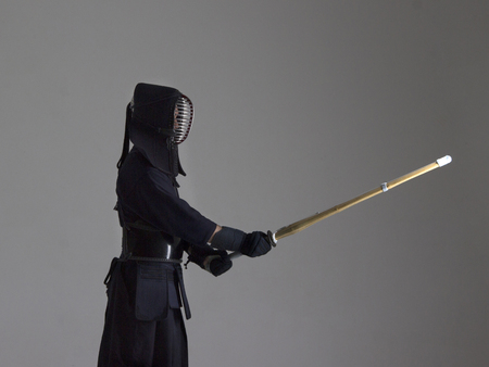 Portrait of man kendo fighter with shinai (bamboo sword). Shot in studio Stock Photo