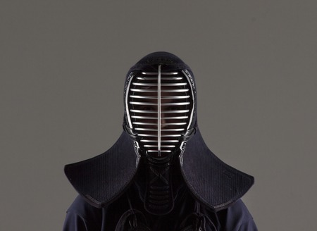 male in tradition kendo armor wearing helmet. shot in studio on grey background