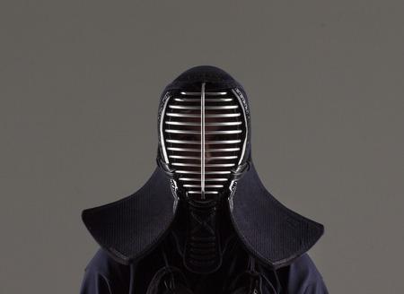 male in tradition kendo armor wearing helmet. shot in studio on grey background
