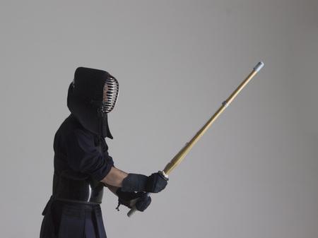 Portrait of man kendo fighter with shinai. Studio shot