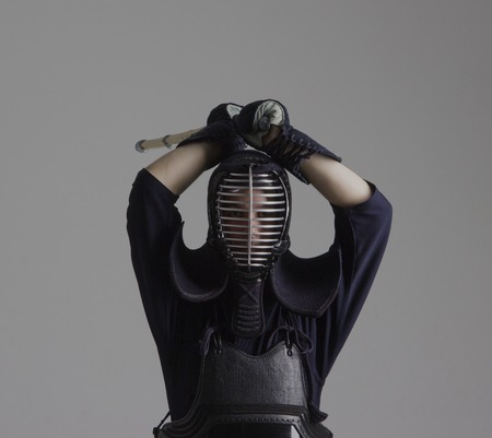 Man is practicing kendo in traditional armor .He swinging with bamboo sword Stock Photo