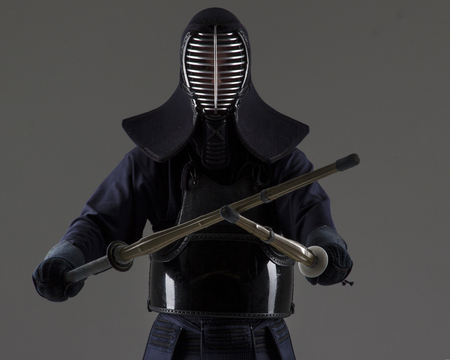 Portrait of man kendo fighter with two bamboo swords in traditional uniform