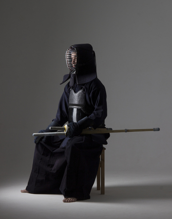 Portrait of man kendo fighter with shinai (bamboo sword) in traditional armor sitting on the chair. Shot in studio.