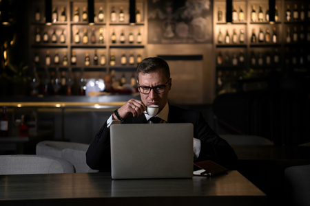 serious handsome elegant caucasian businessman sitting at modern restaurant and typing on his laptop and drinking coffee