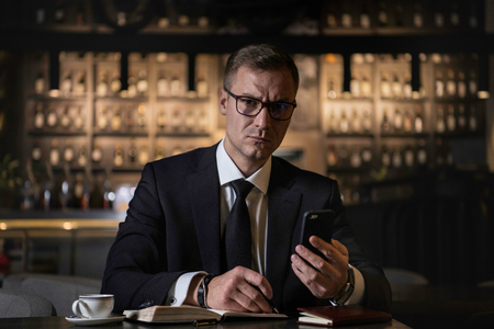 serious handsome elegant businessman sitting at restaurant using his phone and writing the notes in his notebook.