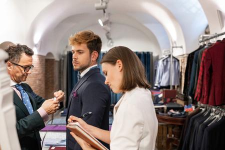 Caucasian man fitting suit at tailors studio.