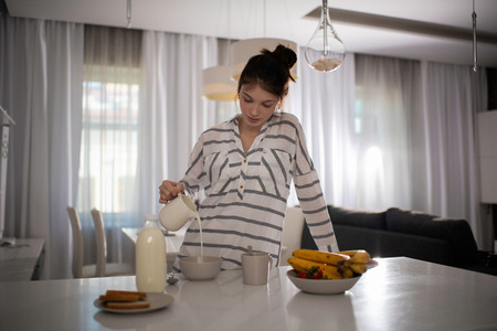 Woman Pourings Milk Into Her Breakfast Cereal Reklamní fotografie