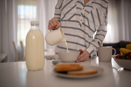 Close of the hand or the Woman Pouring Milk Into Her Cereal