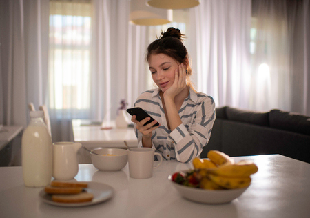 woman sitting at kitchen table with tasty healthy breakfast, listening to music and texting on her smartphone