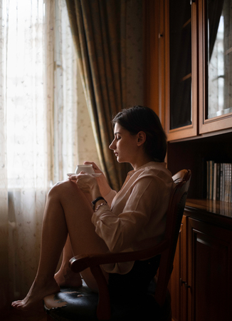 Beautiful Woman drinking coffee At her Home. Reklamní fotografie