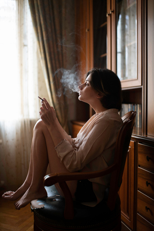 woman sitting at the chair at home and smoking a cigarette.