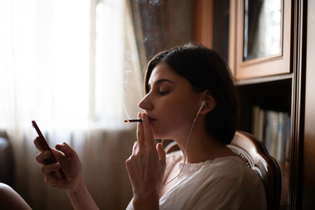 woman sitting at the chair at home, listen to the music and smoking a cigarette