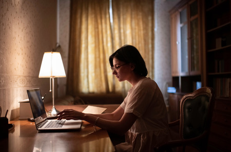 woman working alone at her home with vintage interior