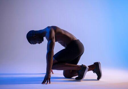 Sprinter African Muscular Man preparing for the start
