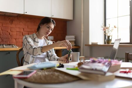 Young schoolgirl using divider while doing homework in kitchen