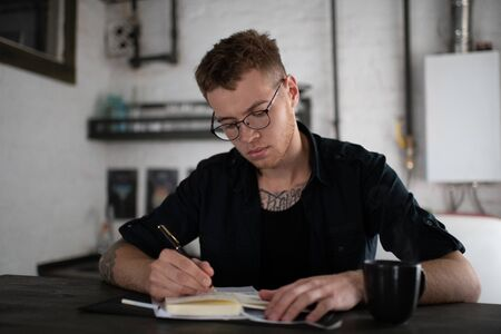 Captivated man in eyeglasses writing in notebook at table