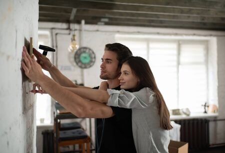 Couple hanging frame on wall.ATTENTION: models are in a slight motion blur due to authenticity of movement - no posing.