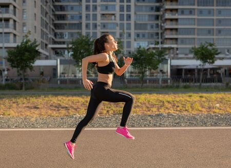 Fit sportive female running on street listening to music