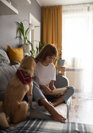 Dog owner reading the book at home