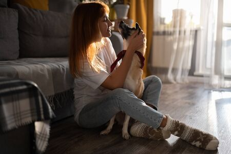 Woman hugging dog on the floor at home 写真素材