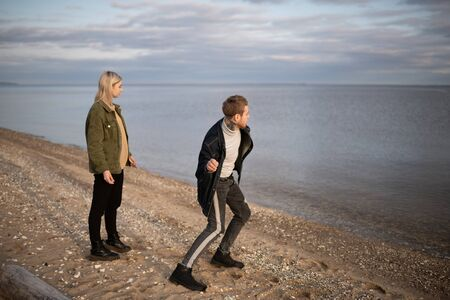 Young hipster couple throwing stones into lake
