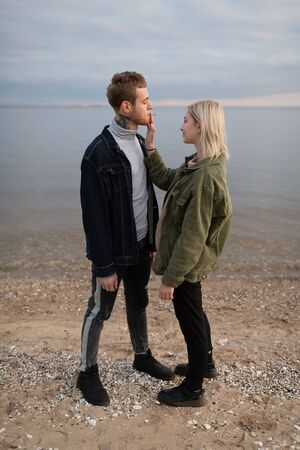 Cool young couple smoking joint on empty coast Stockfoto