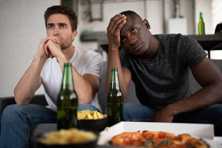 Frustrated multicultural guys watching football match
