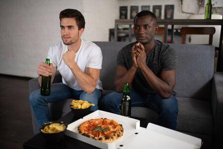 Anxious multiracial men watching football match at home 写真素材