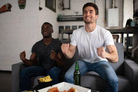 Optimistic guy celebrating goal with black friend