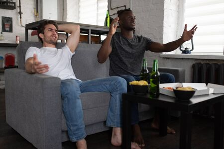 Disappointed football fans gesticulating on sofa 写真素材