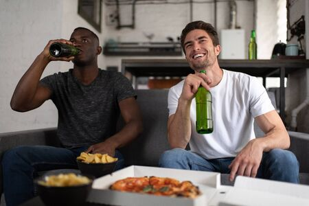 Cheerful multicultural friends drinking beer and watching football match