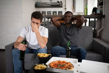Multiracial football fans watching lame match