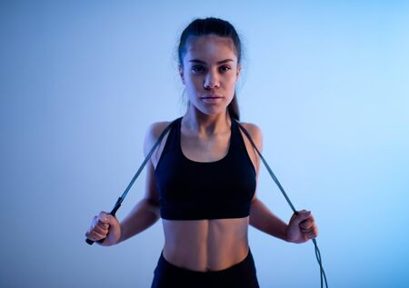 Sporty woman throwing rope over shoulder and pulling