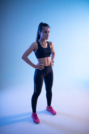 Fit woman in good shape with sporty figure ready for training
