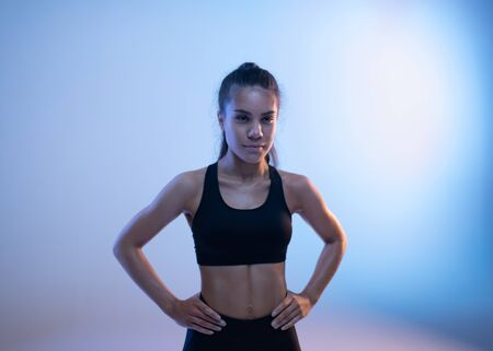 Sporty woman standing with hands aside waiting workout