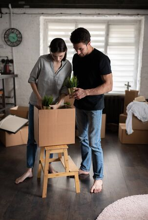 Barefoot couple unpacking plants in new apartment 写真素材