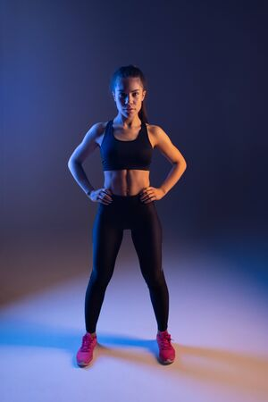 Pleased fit woman with sporty figure ready for training and looking at camera 写真素材